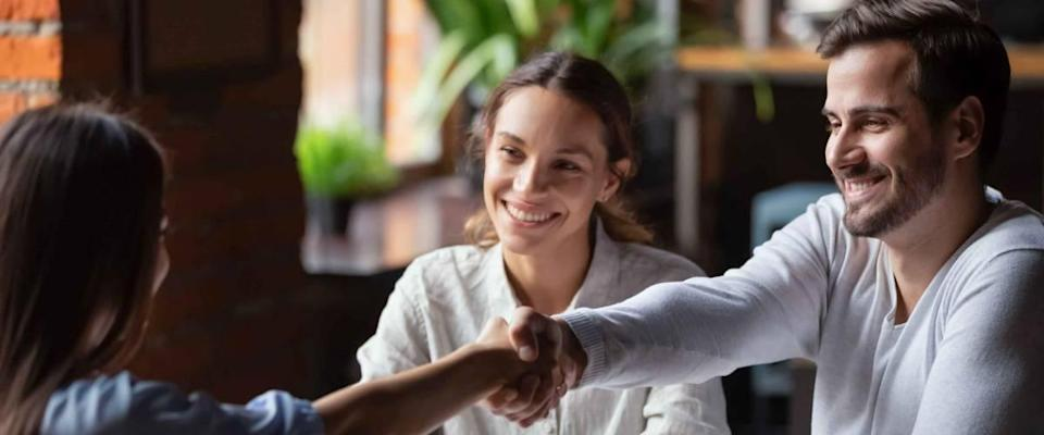 Smiling couple shaking hands with person across the table in an office setting.